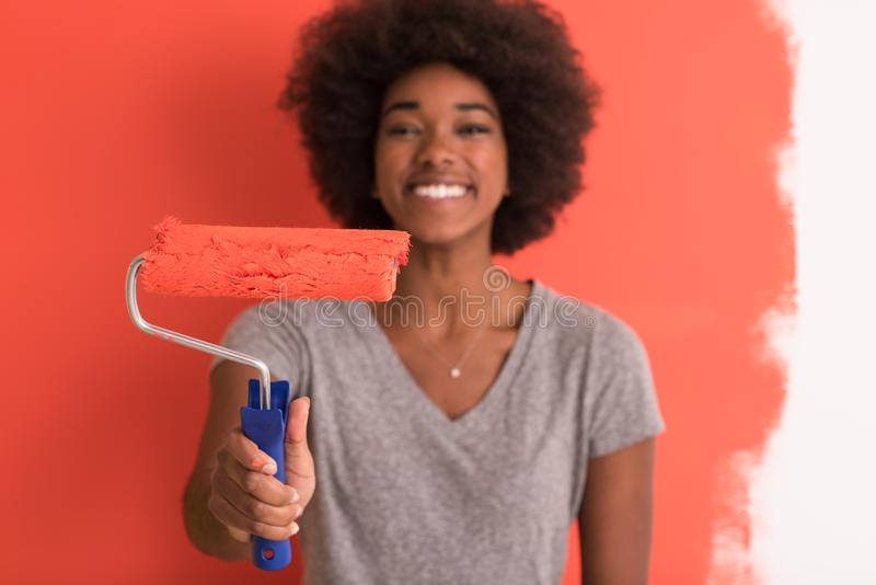 Black woman painting wall. Portrait of a young beautiful African American woman painting wall in her new apartment royalty free stock image