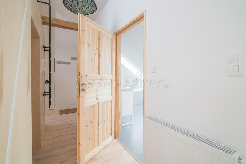 Bright apartment hall with wooden doors. Modern bright flat apartment in the attic royalty free stock photography