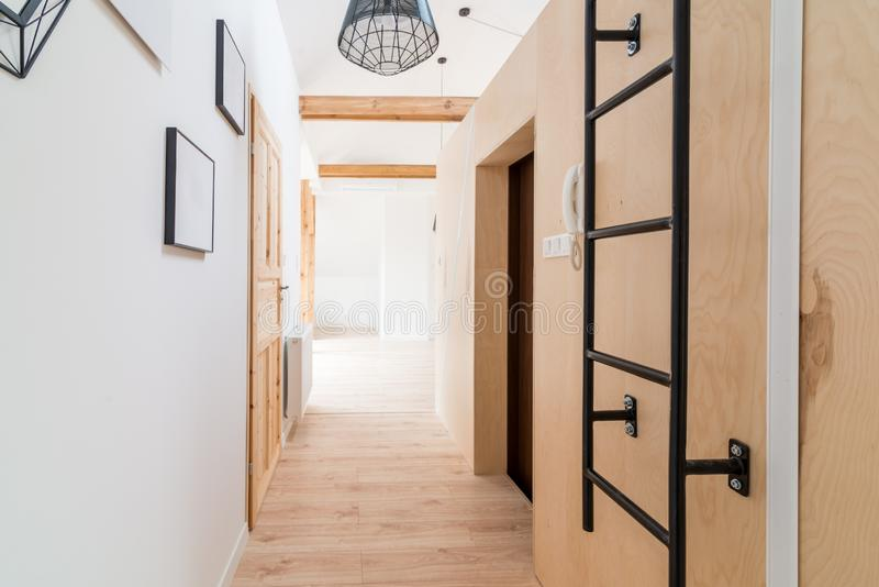 Bright apartment hall with wooden doors. Modern bright flat apartment in the attic stock images