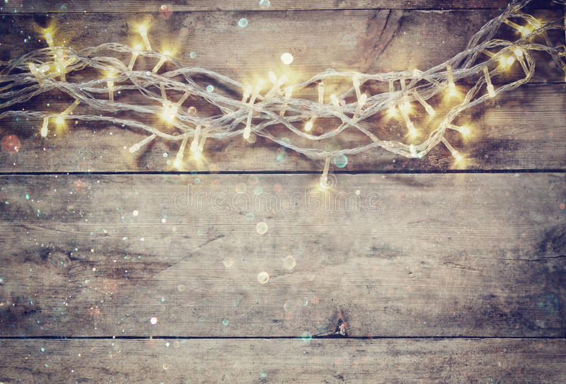 Christmas warm gold garland lights on wooden rustic background. filtered image with glitter overlay. Christmas warm gold garland lights on wooden rustic royalty free stock photo