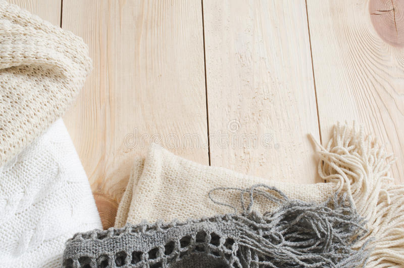 Cozy and soft winter background. Warm knitted clothes on a wooden background. Holidays at home. Selective Focus stock photography