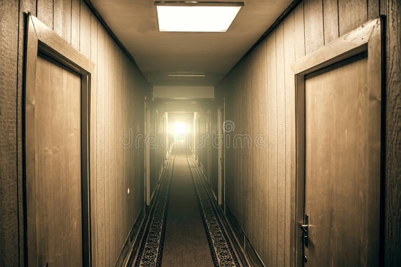 Empty corridor in apartment building with doors and light in the end of hall, perspective. Vintage toned royalty free stock images