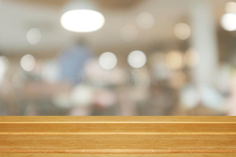 Empty wooden table and blurred modern warm cafe background,. Restaurants. Ready for product montage, bokeh , light royalty free stock images