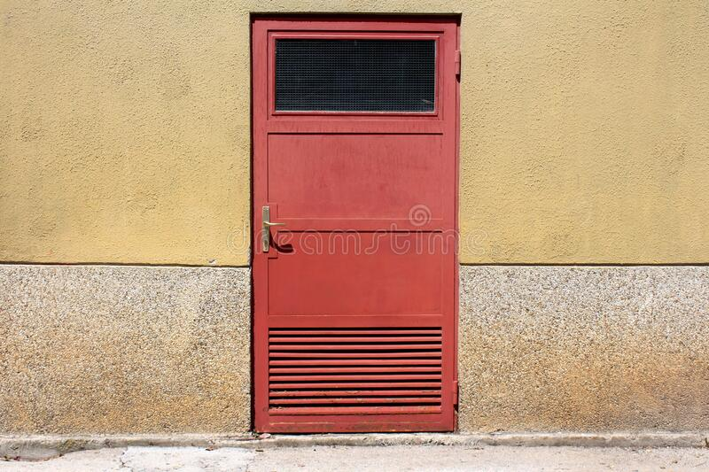 Faded color red metal doors with safety glass window and ventilation openings mounted on old apartment building wall. Next to cracked concrete sidewalk royalty free stock image