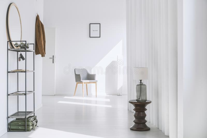 Hall in minimalist white apartment. Simple hall with metal rack and gray armchair in minimalist white apartment royalty free stock image