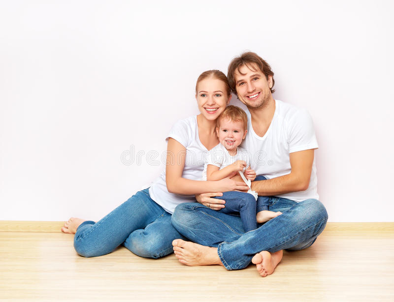 Happy family on floor near empty wall in the apartment bought on mortgage. Happy family on the floor near the empty blank wall in the apartment bought on royalty free stock photography