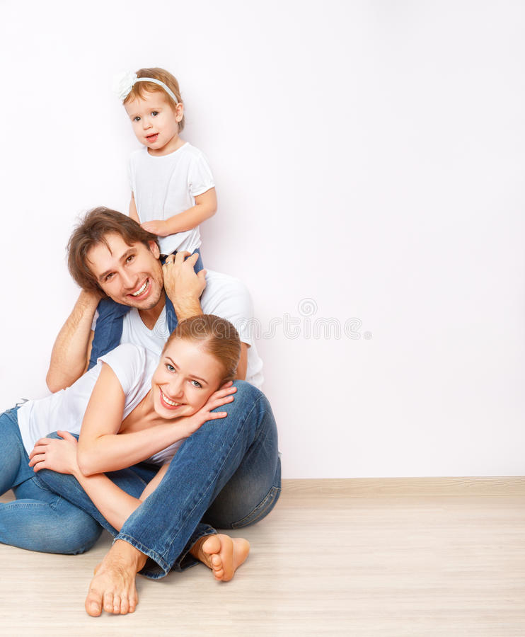 Happy family on floor near empty wall in the apartment bought on mortgage. Happy family on the floor near the empty blank wall in the apartment bought on stock photo