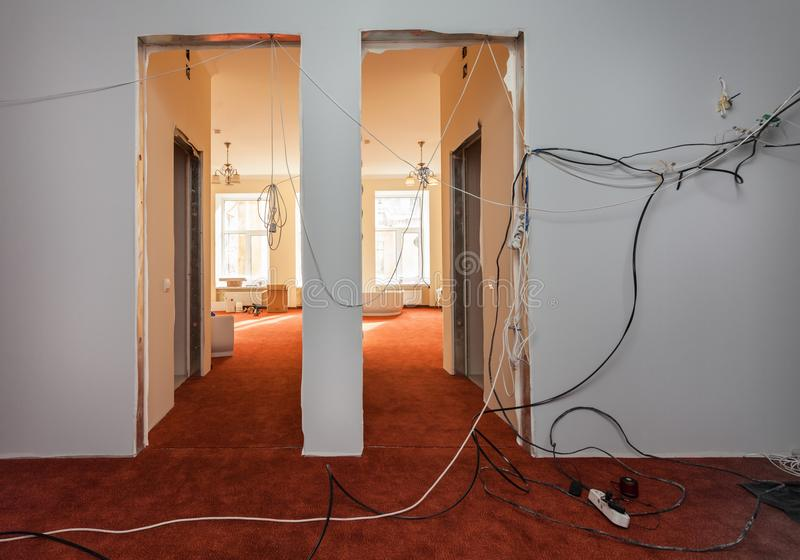 Interior of hall of apartment with temporary electric wires during upgrade or remodeling, renovation, extension,. Restoration, reconstruction and construction stock image