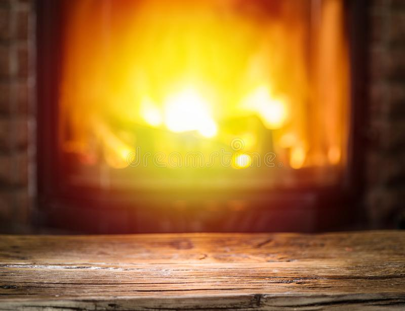 Old wooden table and fireplace with warm fire on the background.  stock photos