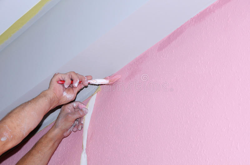 Painting wall of new apartment. painting voids after masking tape. hands in the paint. Close-up stock photos