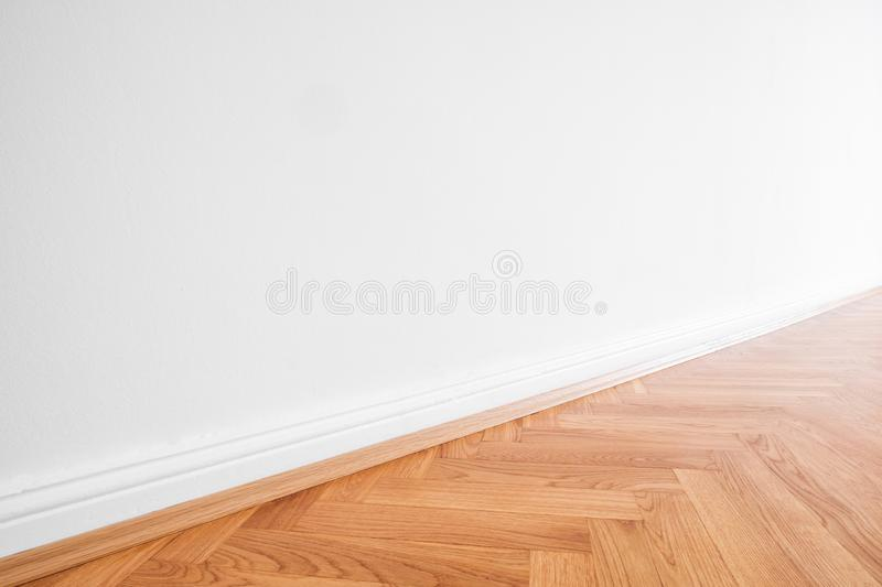 Primed white wall and wooden parquet floor - apartment interior background.  stock photo