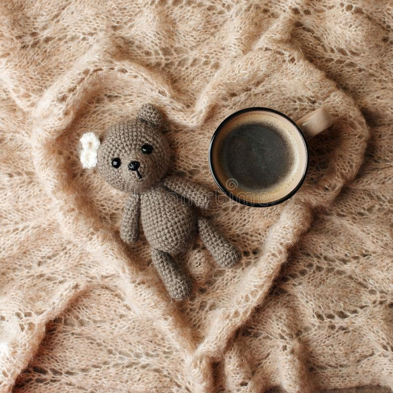 A small knitted baby toy-bear, cup of coffee and a warm blanket shaped heart on wooden background, lazy sleepy morning concept,. Flat lay, top view royalty free stock image