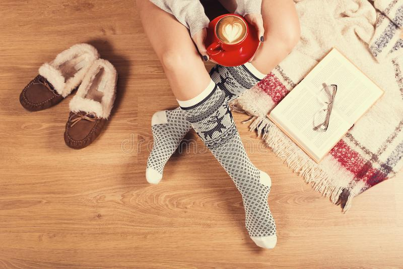 Young woman sitting on the wooden floor with cup of coffee, plaid, cookie and book. Close-up of female legs in warm socks with a. Soft photo of woman on the bed stock photo