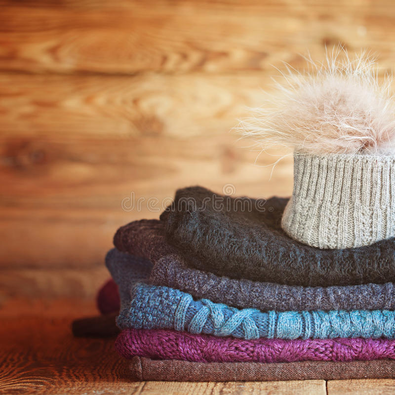 Stack of knitting colorful warm woolen clothes on wooden wall b. Ackground stock photo