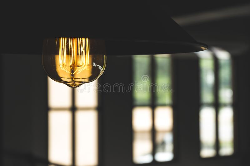 Warm hanging lamp with large windows. On background royalty free stock photo