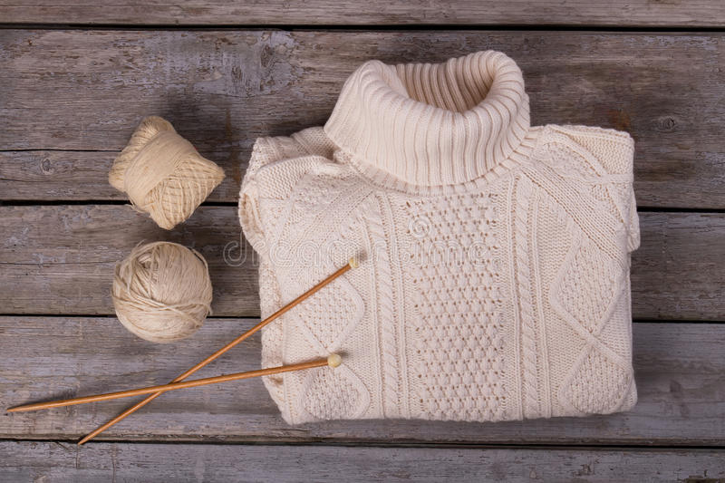 Warm knitted sweater on a wooden background. Winter pullover with yarn and knitting needles. Sweater handmade royalty free stock photos